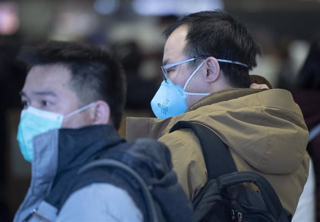 30 January 2020, Frankfurt/Main: Passengers wear face masks as they wait at Frankfurt Airport for the check-in of the Chinese airline Air China. Photo: Boris Roessler/dpa
