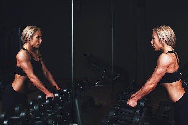 Mujer entrenando musculación se mira al espejo.
