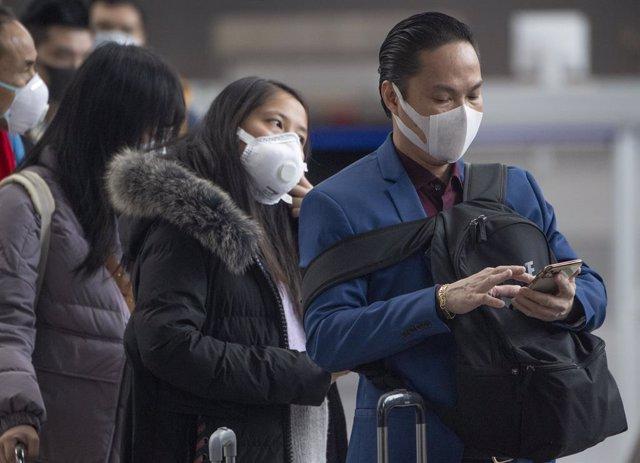 Diversos passatgers esperen amb mascarilles a un aeroport