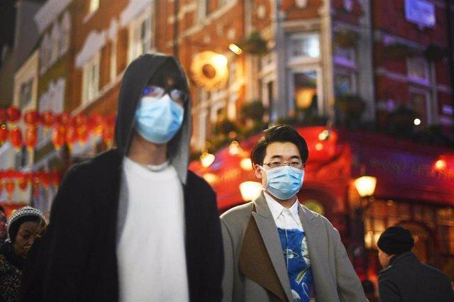 Imagen de dos personas con mascarillas en el barrio de Chinatown, en Londres.