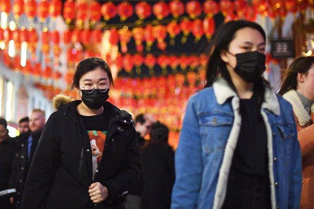 Imagen de dos personas con mascarillas en el barrio londinense de Chinatown.