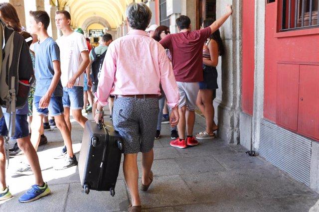 Un turista pasea con una maleta en la Plaza Mayor de Madrid.