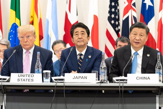 June 28, 2019 - Osaka, Japan: President Donald J. Trump, seated next to Japanese Prime Minister Shinzo Abe, listens as China's President Xi Jinping, right, delivers remarks at the G20 Leaders Special Event on the Digital Economy at the G20 Japan Summit