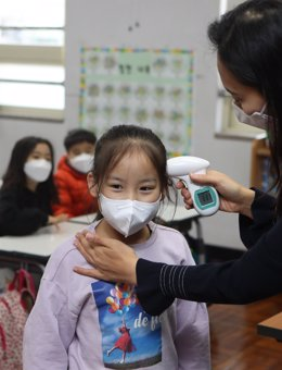 03 February 2020, South Korea, Busan: A teacher measures the temperature of a child at Yangjeong Elementary School, as part of efforts to prevent the spread of a new coronavirus that has broken out in China. Photo: -/YNA/dpa