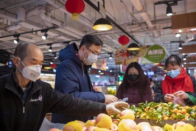 Personas con mascarillas en un mercado de Shanghai
