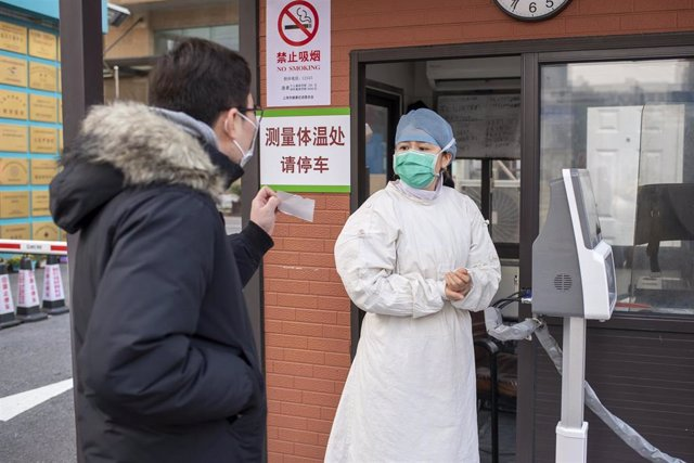 February 3, 2020 - Shanghai, China: A man shows a slip for doctors appoinment to a nurse at the entrance to Xuhui Hospital in the former French Concession. Many Shanghai residents are staying indoors to avoid contagion from the coronavirus which has repor
