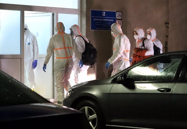 03 February 2020, Slovakia, Banska Bystrica: Medical staff wearing protective suit escort the two Slovak citizens suspected of being coronavirus after being evacuated from Wuhan, China, at F. D. Roosevelt University Hospital, where they will be quarantine
