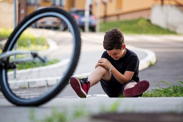 Chico que se ha caido de la bicicleta.