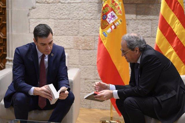 El presidente de la Generalitat, Quim Torra (dech) le regala dos libros al presidente del Gobierno, Pedro Sánchez (izq), antes de su reunión en el Palau de la Generalitat, en Barcelona /Catalunya (España), a 6 de febrero de 2020.