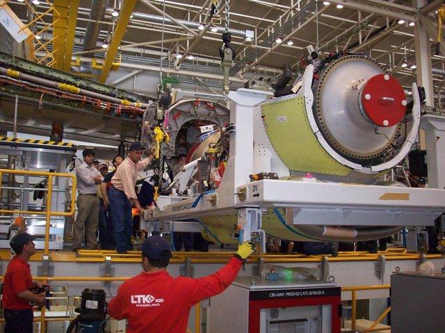 Operarios de LTK dentro de la fábrica, con un motor del A400M