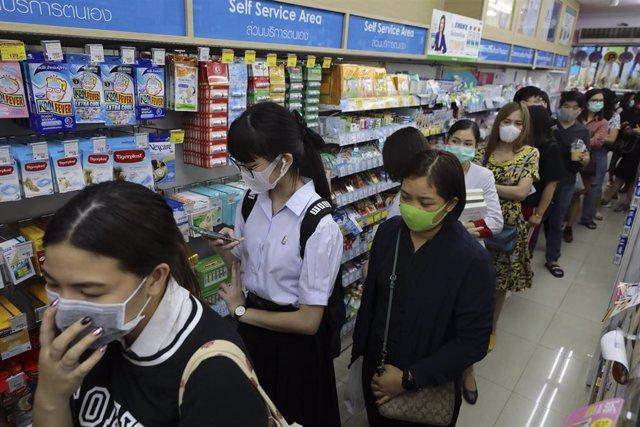 Personas haciendo cola en una farmacia de Bangkok, Tailandia, para comprar máscaras con las que protegerse de una posible infección de coronavirus.