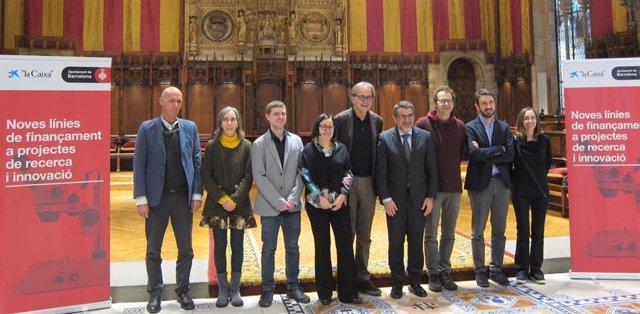 El teniente de alcalde Joan Subirats y el director corporativo de Investigación de La Caixa Àngel Font, con los proyectos ganadores de ayudas a la ciencia