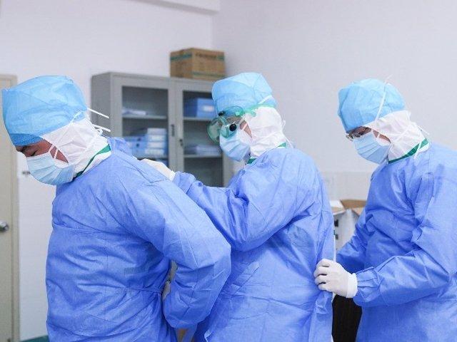 Trabajadores médicos se ayudan mutuamente para ponerse trajes protectores contra el coronavirus.