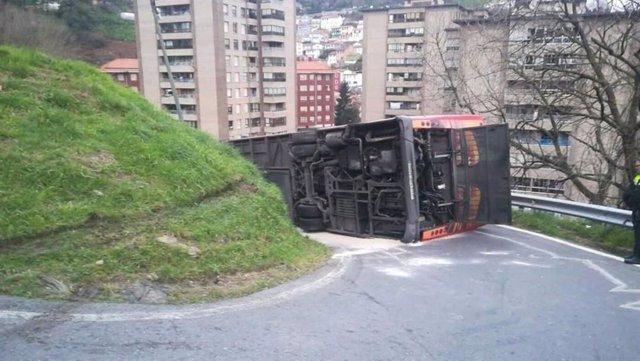 Imagen del autobus de Bilbobus volcado en la Estrada Masustegui de Bilbao