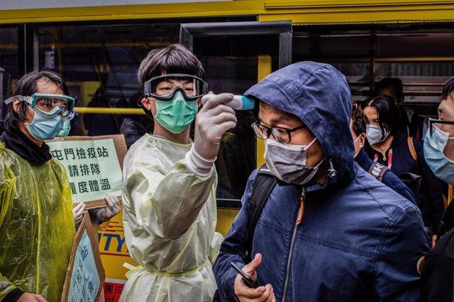 Un home mesura la temperatura a un altre a Hong Kong pel brot del nou coronavirus.