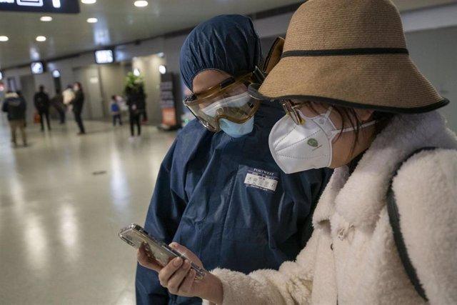Imagen de dos personas en China con mascarillas tras el brote del nuevo coronavirus.