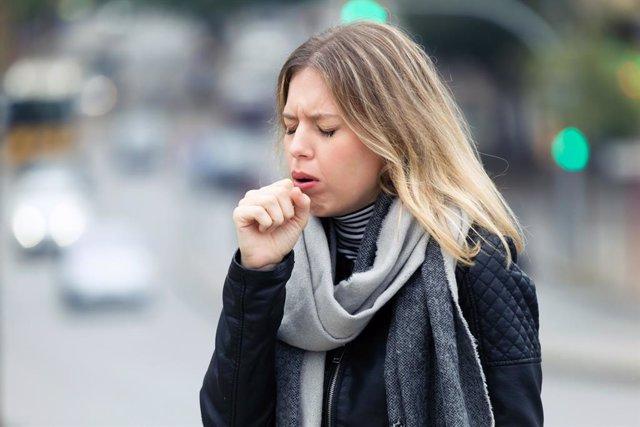Mujer tosiendo en la calle.