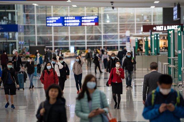 Travellers and airline crew members are seen wearing surgical masks as a protective measure from the deadly coronavirus at the Hong Kong international airport.