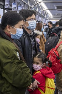A young girl is calmed by her parents as they wear protecive masks on board an airport transit bus.