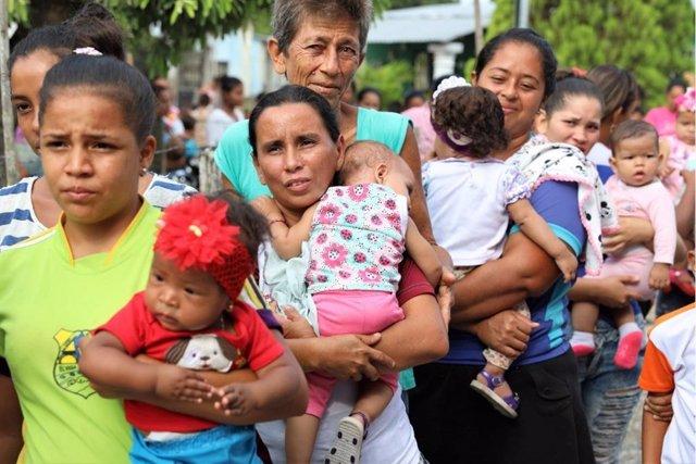 Madres con sus hijos esperan a recibir atención en Venezuela