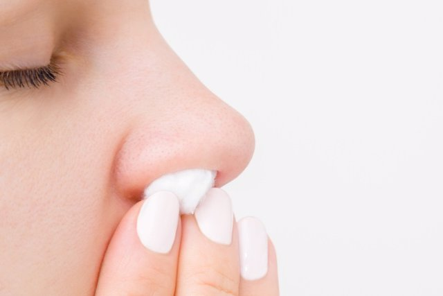 Young woman fingers using cotton wool for stopping blood from nose. Isolated on light gray background. Close up. Side view. Empty place for text.