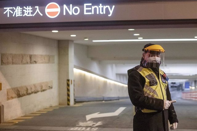 February 10, 2020, Shanghai China - A security guard in a surgical mask and a clear plastic visor holds an electronic thermometer and stands outside car park at the Kerry Center luxiury mall on West Nanjing Road, usually one of Shanghai's busiest streets.