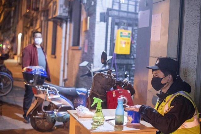 February 10, 2020, Shanghai China - A security guard in a surgical mask sitsbehind a table at the entrance to a residential laneway as he waits to register people and check them for signs of the coronavirus. Although today was China's first day offically