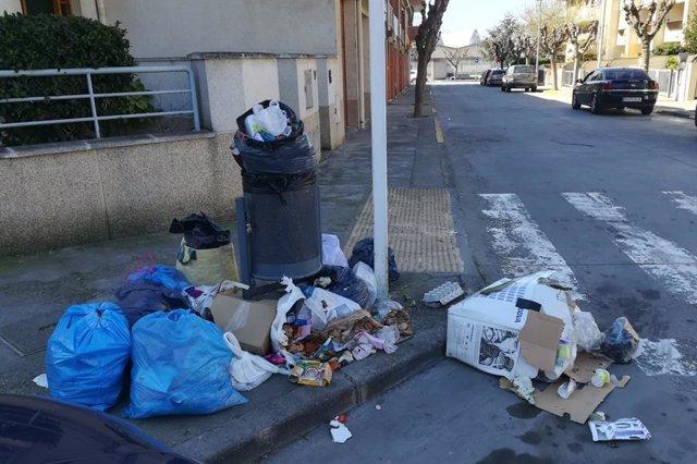 Escombraries al costat d'una paperera.