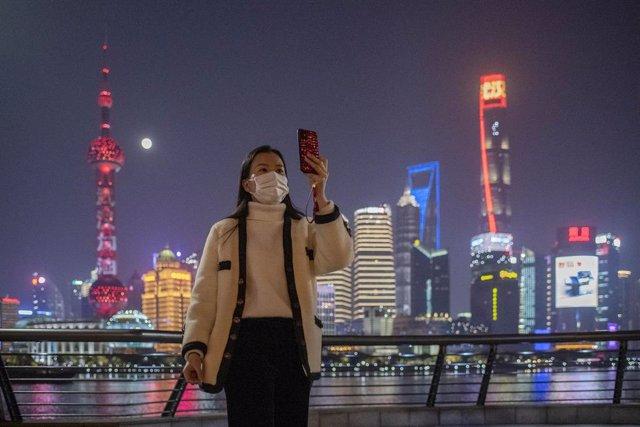 Una mujer con máscara se saca una foto en Shangái.