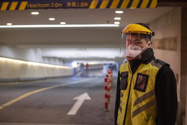February 10, 2020, Shanghai China - A security guard in a surgical mask and a clear plastic visor outside car park at the Kerry Center luxiury mall on West Nanjing Road, usually one of Shanghai's busiest streets. (Dave Tacon/Contacto)
