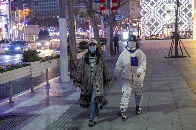 Dues dones es protegeixen amb màscara del nou brot de coronavirus a Xangai.