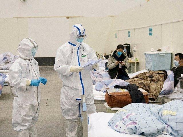 """El personal médico verifica el estado de un paciente en un hospital temporal convertido de """"Wuhan Livingroom"""" en Wuhan, provincia de Hubei, en el centro de China, el 10 de febrero de 2020."""