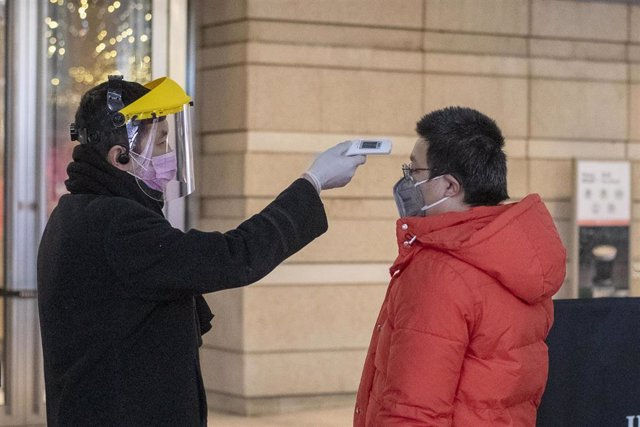 February 10, 2020, Shanghai China - A security guard in a surgical mask and a clear plastic visor uses an electronic thermometer to take the temperature of a man at the entrance to the Kerry Center office block on West Nanjing Road, usually one of Shangha