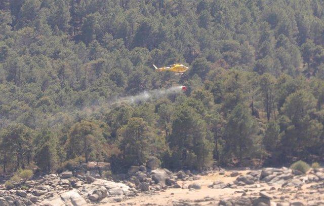 Un helicóptero recoge agua del pantano de Burguillos, Ávila para extinguir un fuego.