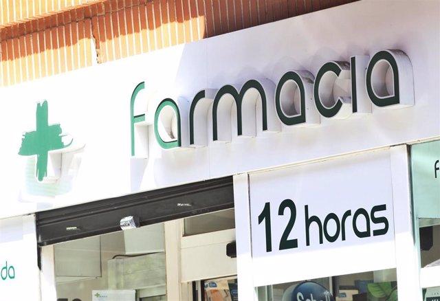Puerta principal de una farmacia en la que se lee '12 horas'.