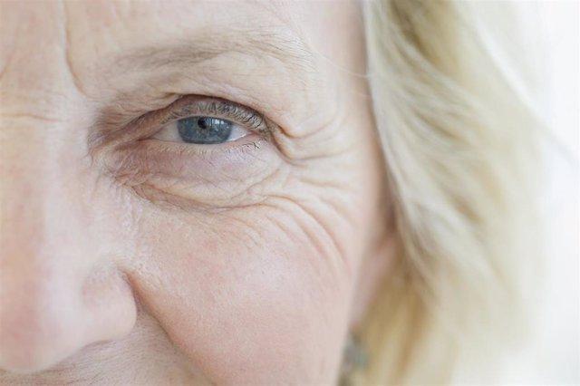 Patas de gallo señora mayor. Arrugas en los  ojos. Ojos azules. Mujer mayor rubia