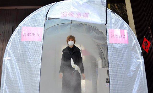 Una mujer camina a través de un canal de desinfección situado en la ciudad de Hefei, en el oeste de China.
