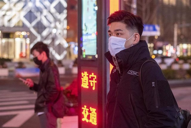 February 10, 2020, Shanghai China - Two men protective masks wait at a pedestrian crossing on West Nanjing Road, usually one of Shanghai's busiest streets. Although today was China's first day offically back at work after Chinese New Year holidays the str