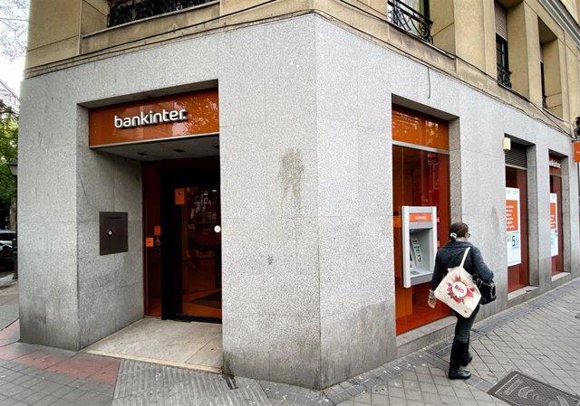 Una mujer camina junto a una oficina del Bankinter en Madrid.