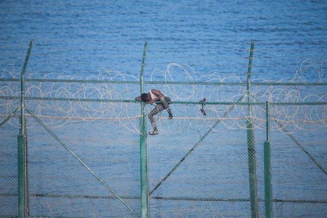 En la imagen, uno de los 153 migrantes, que han entrado en Ceuta saltando su doble valla en la primera incursión en grupo en un año; se aferra a las concertinas.