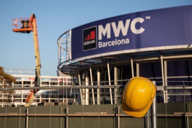 Un casco de obra amarillo colgado en una de las vallas que cierran el recinto del Mobile World Congress (MWC) durante el desmantelamiento de los stands tras la cancelación de la feria.