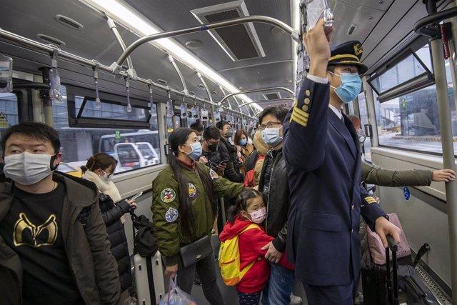 Unas personas viajan portando mascarillas de seguridad en un transporte del aeropuerto de traslado de pasajeros.