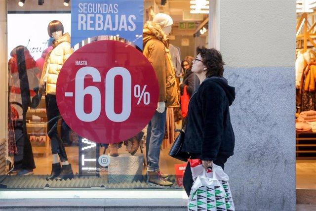 Una mujer pasea junto a una tienda de moda , en la que se ofertan las segundas rebajas con ofertas de hasta el 60%.