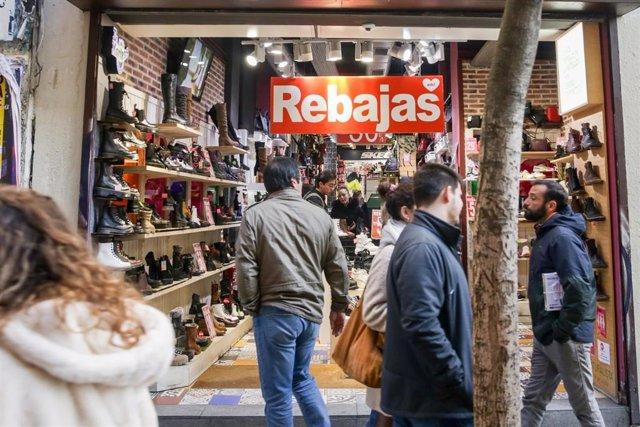 Varias personas pasean junto a una tienda de zapatos de Madrid, donde ya ha empezado la temporada de rebajas.
