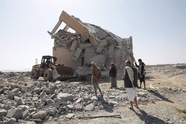 Personas junto a un edificio destruido en un bombardeo aéreo en Yemen