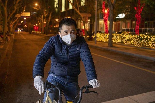 Ciclista con mascarilla en Shangai (China) para prevenir el contagio de coronavirus
