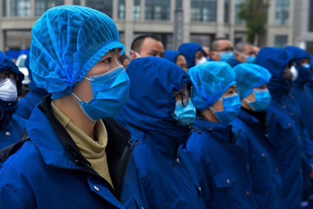 14 February 2020, China, Hubei: Members of a medical team in surgical masks arrive to support the treatment of patients who have contracted coronavirus. Photo: Hu Xuejun/SIPA Asia via ZUMA Wire/dpa