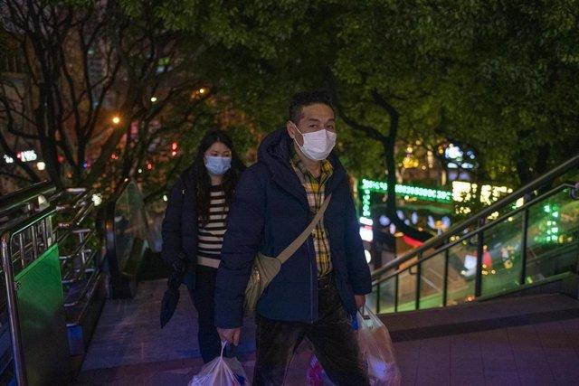 Residentes hacen la compra con mascarillas.