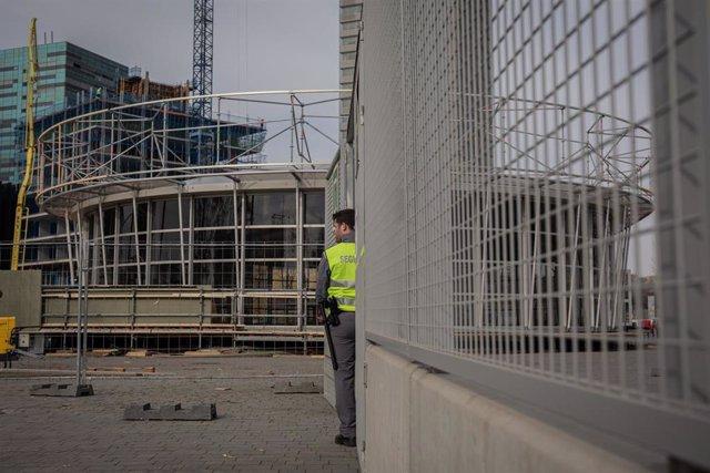 Un guardia de seguridad vigila la entrada al recinto del Mobile World Congress (MWC) durante el desmantelamiento de los stands de la feria tras su cancelación por la crisis del coronavirus y las anulaciones de empresas, en Barcelona/Catalunya (España) a 1