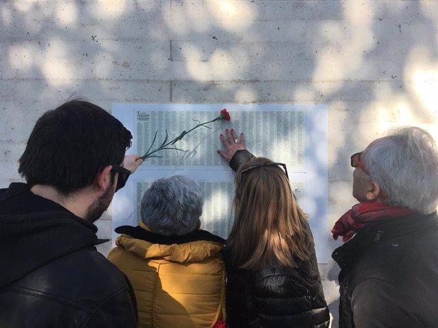 Familiares de las víctimas buscan los nombres de sus seres queridos en el memorial de Valladolid.